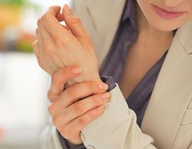 femme qui se tient le bras à cause de l'arthrose